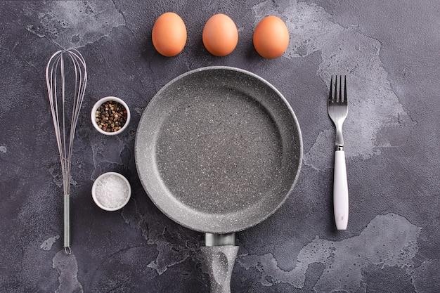 Składniki i naczynia do przyrządzenia jajecznicy leżą na ciemnym kamiennym tle