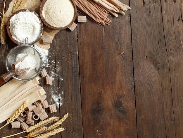 Składniki i naczynia do robienia makaronu na tle drewnianych