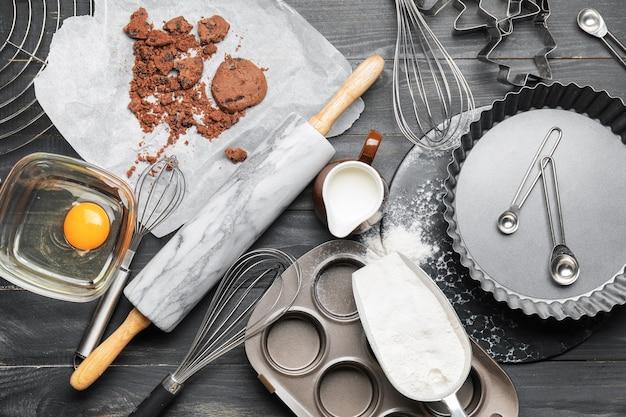 Składniki i przybory do gotowania wypieków na ciemnym drewnianym tle