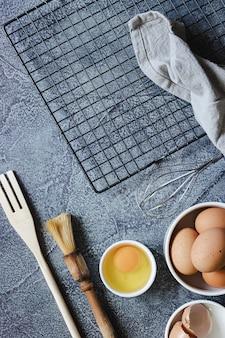 Składniki i przybory do przygotowania ciasta na niebieskiej powierzchni. jajka, mąka, cynamon, mleko. widok z góry. skopiuj miejsce