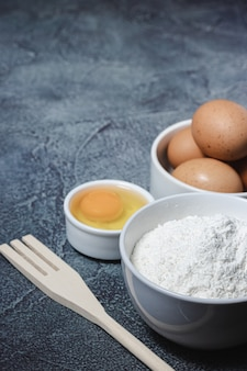 Składniki i przybory do przygotowania ciasta na niebieskiej powierzchni z teksturą. jajka, mąka, cynamon, mleko. widok z góry. skopiuj miejsce