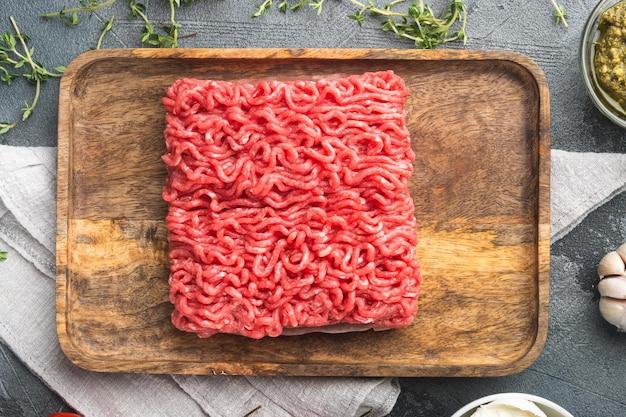 Składniki klopsika cielęcina lub mieszane domowe mięso mielone z zestawem przypraw i ziół, na szarym kamiennym tle, widok z góry płasko leżący