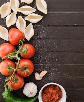 Składniki kuchni włoskiej. jedzenie dietetyczne lub wegańskie. widok z góry włoskiej pasty, pomidorów, czosnku, zielonej papryki i makaronu pomidorowego.