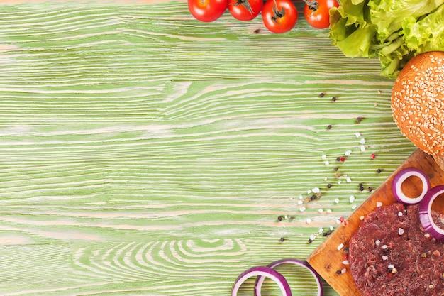 Składniki makaronu i przyprawa na zielonej powierzchni drewnianych