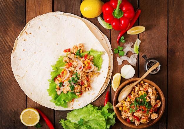 Składniki na burritos owijają mięso z kurczaka, kukurydzę, pomidory i paprykę na drewnianym stole. widok z góry