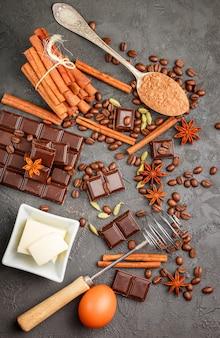 Składniki na desery - ciemna czekolada, kakao, kawa, cynamon, anyż, kardamon, przyprawy i przyprawy na czarnym tle, widok z góry