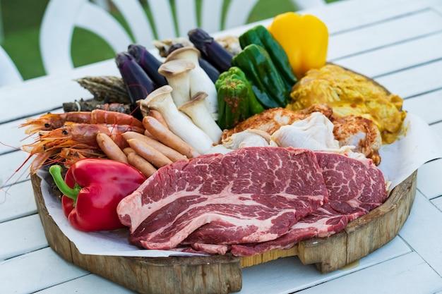 Składniki na grilla z warzywami i mięsem ułożone na stole na zewnątrz