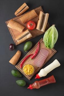 Składniki na kanapkę na desce. domowe kanapki z szynką i warzywami.