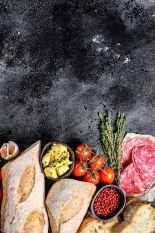Składniki na kanapkę z masłem, wędzonym mięsem, bagietką, pomidorami koktajlowymi, parmezanem, czosnkiem i przyprawami. widok z góry. skopiuj miejsce