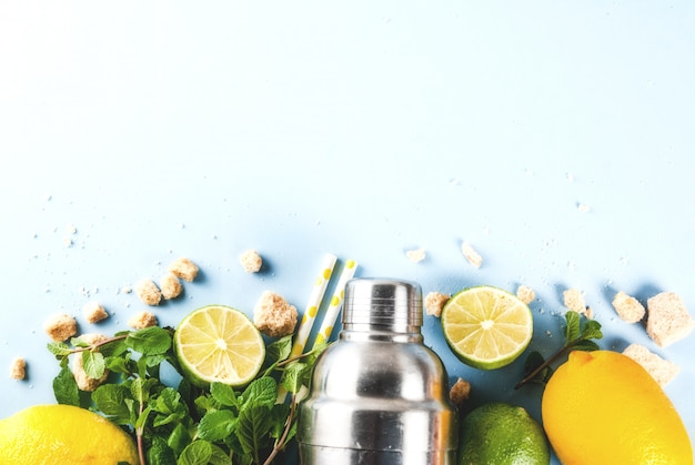 Składniki na koktajl mojito lub lemoniadę - cytryna, limonka, mięta, cukier, z wytrząsarką i słomkami koktajlowymi. na jasnoniebieskim widoku z góry copyspace