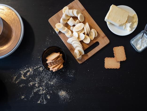 Składniki na kruche ciasto z bananem i karmelem, czarny drewniany stół w kuchni, produkty przygotowane na pyszny deser ze śmietaną, domowa kuchnia