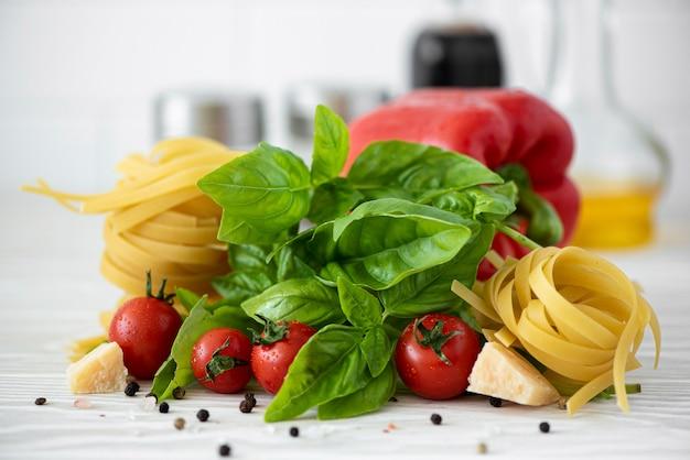 Składniki na makaron fettuccine z pomidorami, przyprawami i bazylią