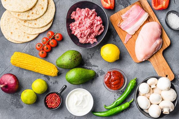 Składniki na meksykańskie tacos z kurczakiem i wołowiną myszy, zioła kukurydziane, salsa, na szarym tle z teksturą, widok z góry.