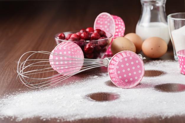 Składniki na muffiny: mrożona wiśnia w talerzu, jajka, mąka na ciemnym drewnianym stole