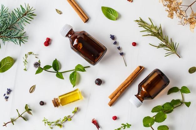 Składniki na olejek eteryczny. różne zioła i butelki olejku, białe tło, flatlay.