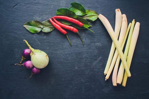 Składniki na popularną tajską zupę tom-yum kung. wapno, galangal, czerwone chili, pomidor cherry, trawa cytrynowa i liść limonki kaffir na czarnej desce. leżał płasko. widok z góry.