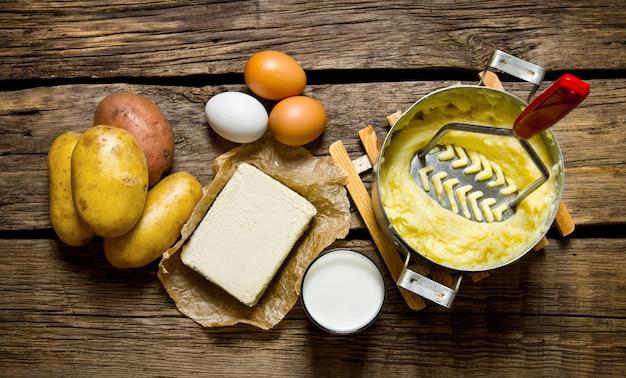Składniki na puree ziemniaczane - jajka, mleko, masło i ziemniaki na podłoże drewniane.