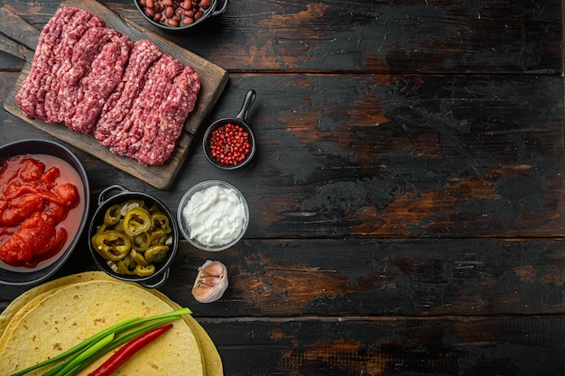 Składniki na quesadillę z tortillą z kurczakiem, kukurydzą, kurczakiem, cebulą, pomidorami i papryką, ser, na starym ciemnym drewnianym stole, widok z góry na płasko