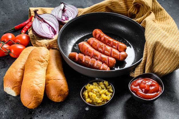 Składniki na różne domowe hot dogi, ze smażoną cebulą, chili, pomidorami, keczupem, ogórkami i kiełbasą. widok z góry