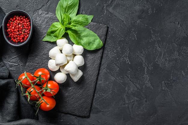Składniki na sałatkę caprese, ser mini mozzarella, liście bazylii i pomidorki koktajlowe. czarne tło