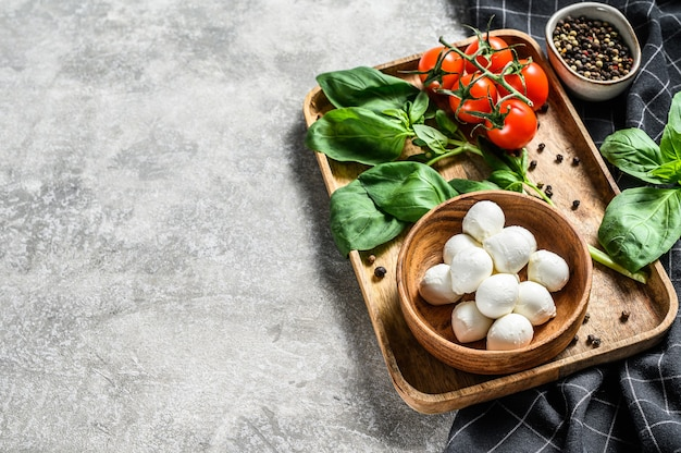 Składniki na sałatkę caprese, ser mini mozzarella w drewnianej misce z liśćmi bazylii i pomidorkami koktajlowymi. szare tło