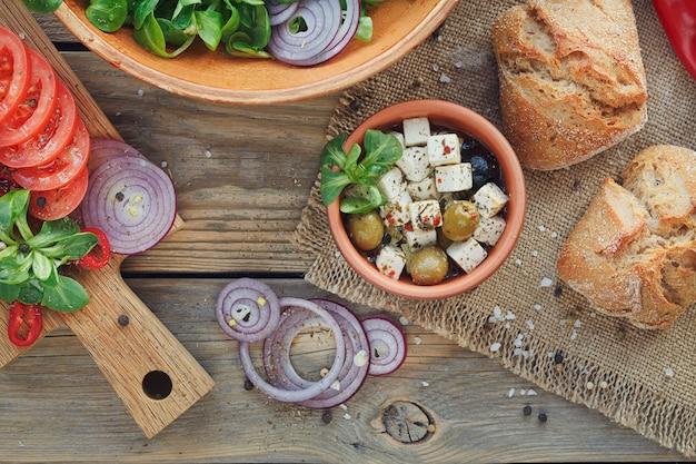 Składniki na sałatkę warzywną na drewnianej powierzchni: liście sałaty, pomidory, papryka czerwona, cebula, oliwki, oliwa i ser