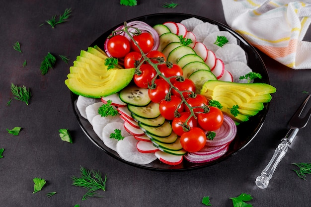 Składniki na sałatkę warzywną, świeże pomidory, ogórek, awokado, sałatę, cebulę