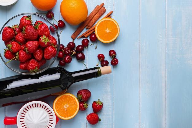 Składniki na sangrię. butelka wina, jagody, pomarańcze, wyciskarka na drewnianym stole, widok z góry