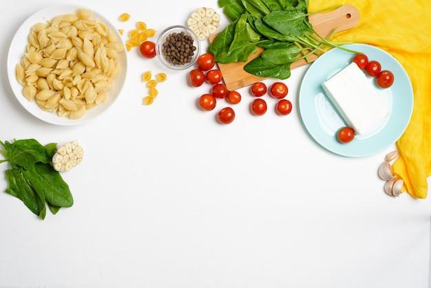Składniki na ser feta pieczony w piecu z pomidorami i makaronem, pieprz czosnek na jasnym tle widok z góry.