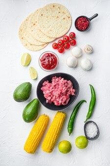 Składniki na tacos z mielonym mięsem wołowym, tortille kukurydziane, chili, awokado, na białym tle. widok z góry.