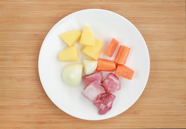 Składniki na wrzącej zupy (plastry marchew, cebula, kości wieprzowe i ziemniaków) w białej płytce o
