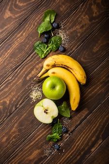 Składniki na zdrowe śniadanie detox green smoothie bowl z banana, jabłek i szpinaku na drewnianej powierzchni. widok z góry