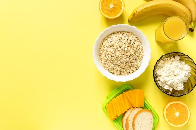 Składniki na zdrowe śniadanie. płatki owsiane, produkty mleczne i owoce na żółtej powierzchni, lato.
