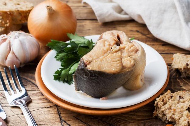 Składniki na zupę z łososia, kromki chleba, cebuli i czosnku z zieleniną na drewnianym stole.