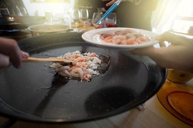 Składniki paelli, krewetki, na patelni. tradycyjne hiszpańskie jedzenie zwykle przygotowywane z ryżu, mięsa, owoców morza