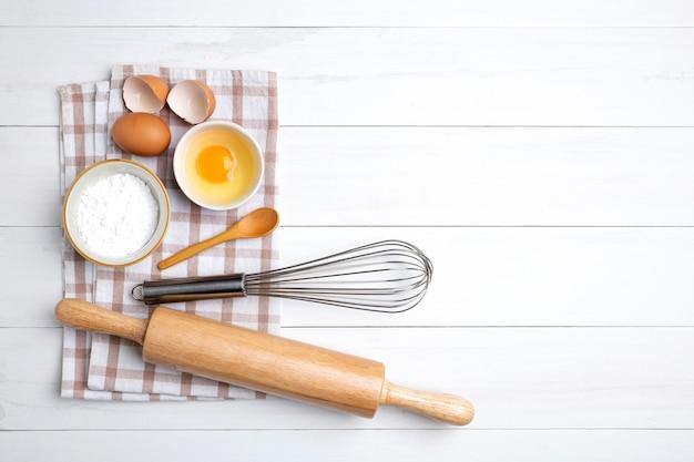 Składniki piekarnicze kłosy pszenicy i miska mąki, jajko, wałek do ciasta, trzepaczka do jajek na białym tle