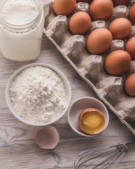 Składniki piekarnicze - mąka, jajka, mleko, żółtko na stole. zbliżenie stonowane zdjęcie