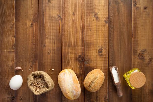Składniki piekarnicze na drewnianym stole w tle, widok z góry