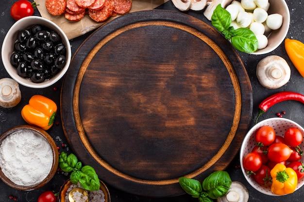 Składniki pizzy na ciemnym tle i okrągła deska do krojenia. pepperoni, mozzarella, pomidory, oliwki, grzyby i mąka to różne produkty do robienia pizzy i makaronu