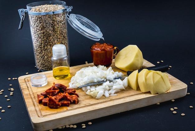 Składniki pomidor, cebula, chorizo i ziemniaki. domowy przepis na hiszpańskie danie z soczewicy