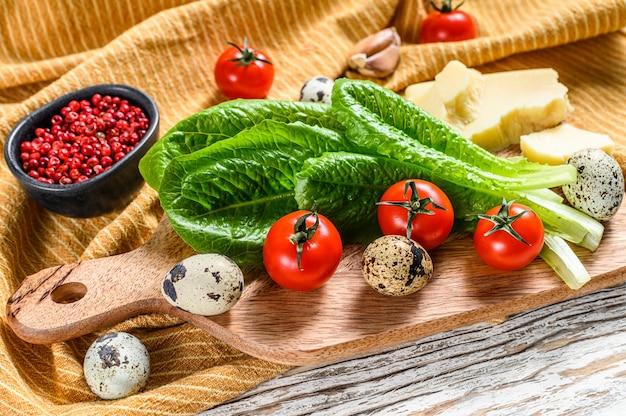 Składniki sałatka cezar na desce do krojenia. sałata rzymska, pomidory koktajlowe, jajka, parmezan, czosnek, pieprz. widok z góry