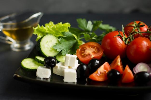 Składniki sałatki cezar. świeże warzywa, ser i oliwa z oliwek.