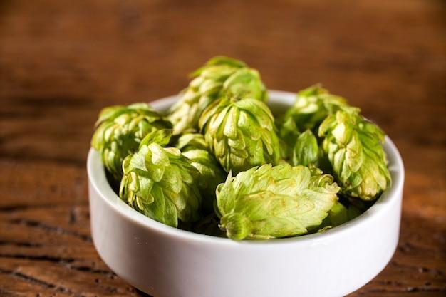 Składniki warzenia piwa szyszki chmielowe w białej misce na drewniane tła. koncepcja browaru piwnego.