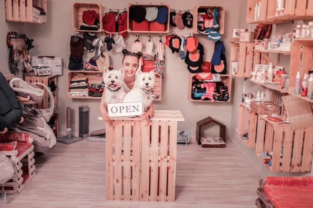 Sklep dla zwierząt. ciemnowłosa piękna młoda kobieta uśmiecha się podczas otwierania sklepu dla zwierząt