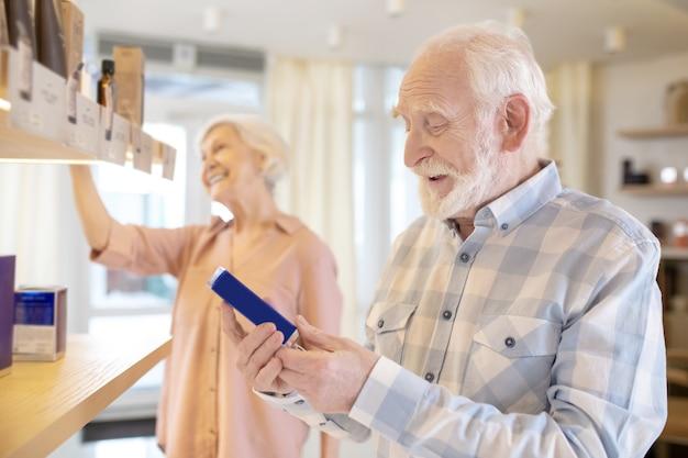 Sklep kosmetyczny. starsza para wybiera kosmetyki w salonie piękności