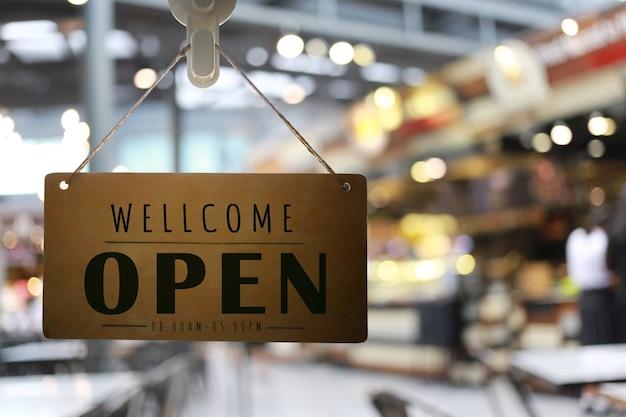 Sklep otwarty z szyldem, restauracja pokazuje stan otwarcia.