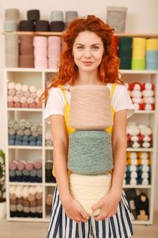 Sklep tekstylny. piękna rudowłosa pracownica słynnego sklepu tekstylnego