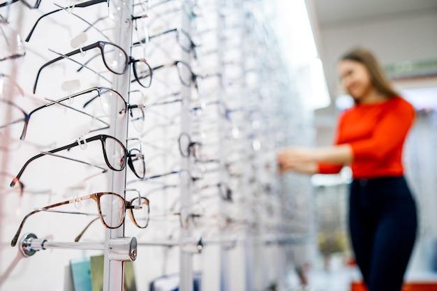 Sklep z okularami. stań z okularami w sklepie z optyką. prezentacja z okularami w nowoczesnym sklepie okulistycznym. zbliżenie. kobieta na zamazanym tle.