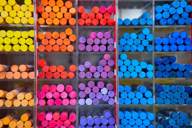 Sklep ze sztuką kolorowych kredek pastelowych w drewnianych komórkach. artspace, warsztaty, koncepcja kreatywności. sztuka współczesna. styl abstrakcyjne tło