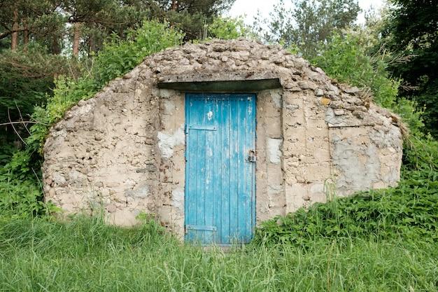 Sklepienie gospodarcze z niebieską drewnianą fasadą